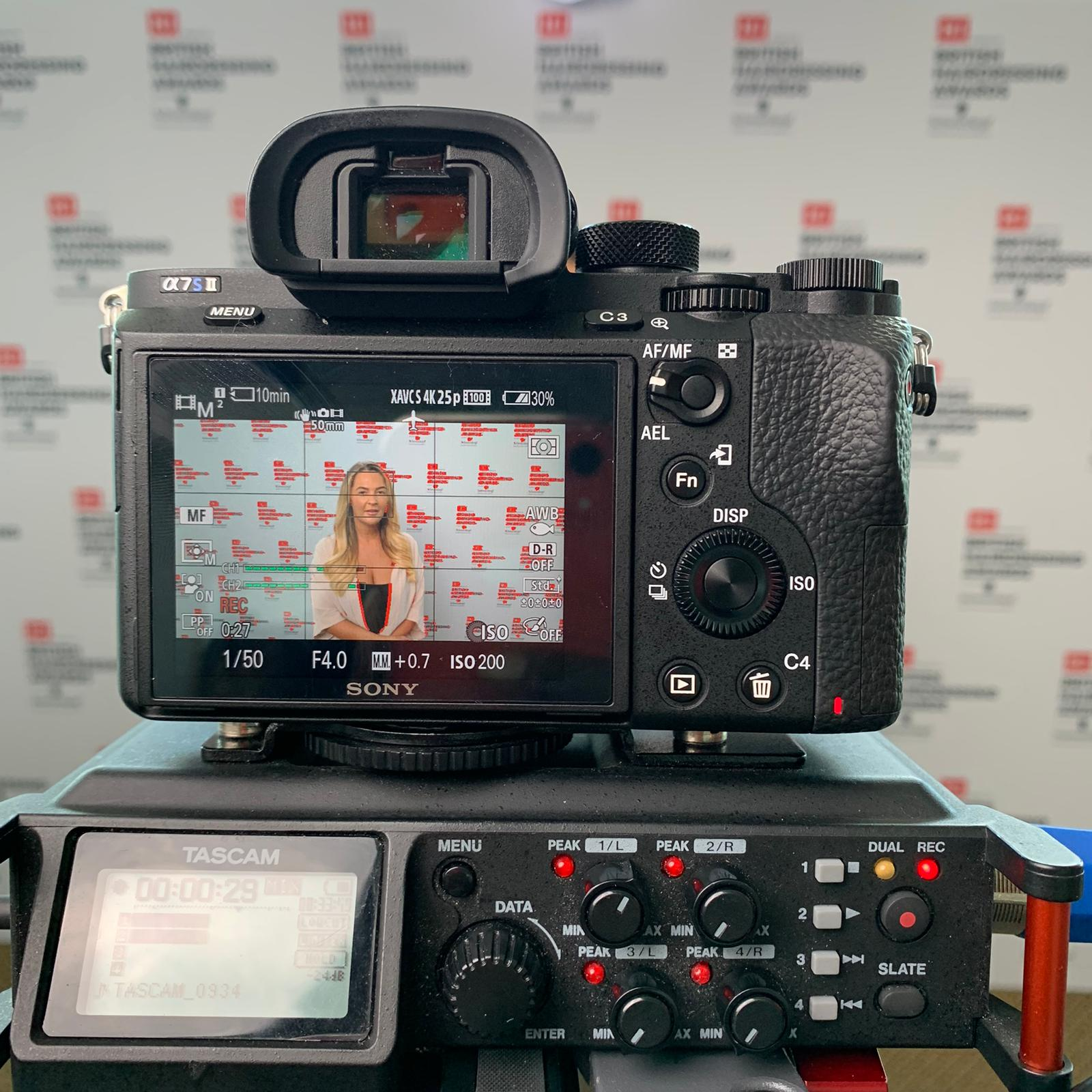 Digital camera mounted on an editing device, the display showing a woman in front of the BHA logo wall