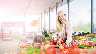Food shopping woman in front of fruit and vegetable shelves