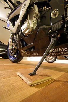 Um Punktbelastungen zu vermeiden, stehen die Motorradständer auf kleinen Dielenstücken