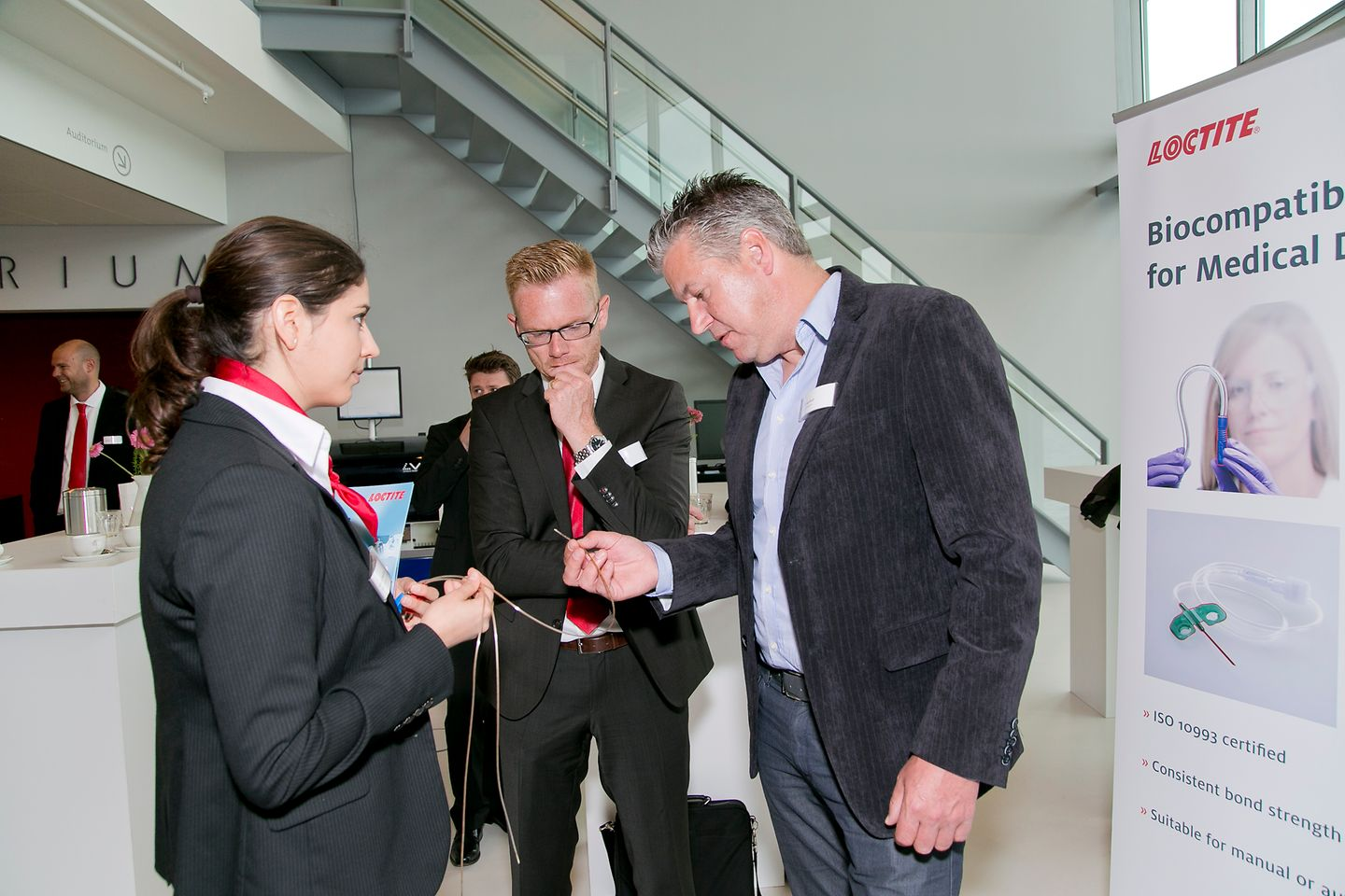 Henkel experts Lucie Heidar and Maarten Adolfs explain the applications of biocompatible adhesives for medical devices to a customer (right).