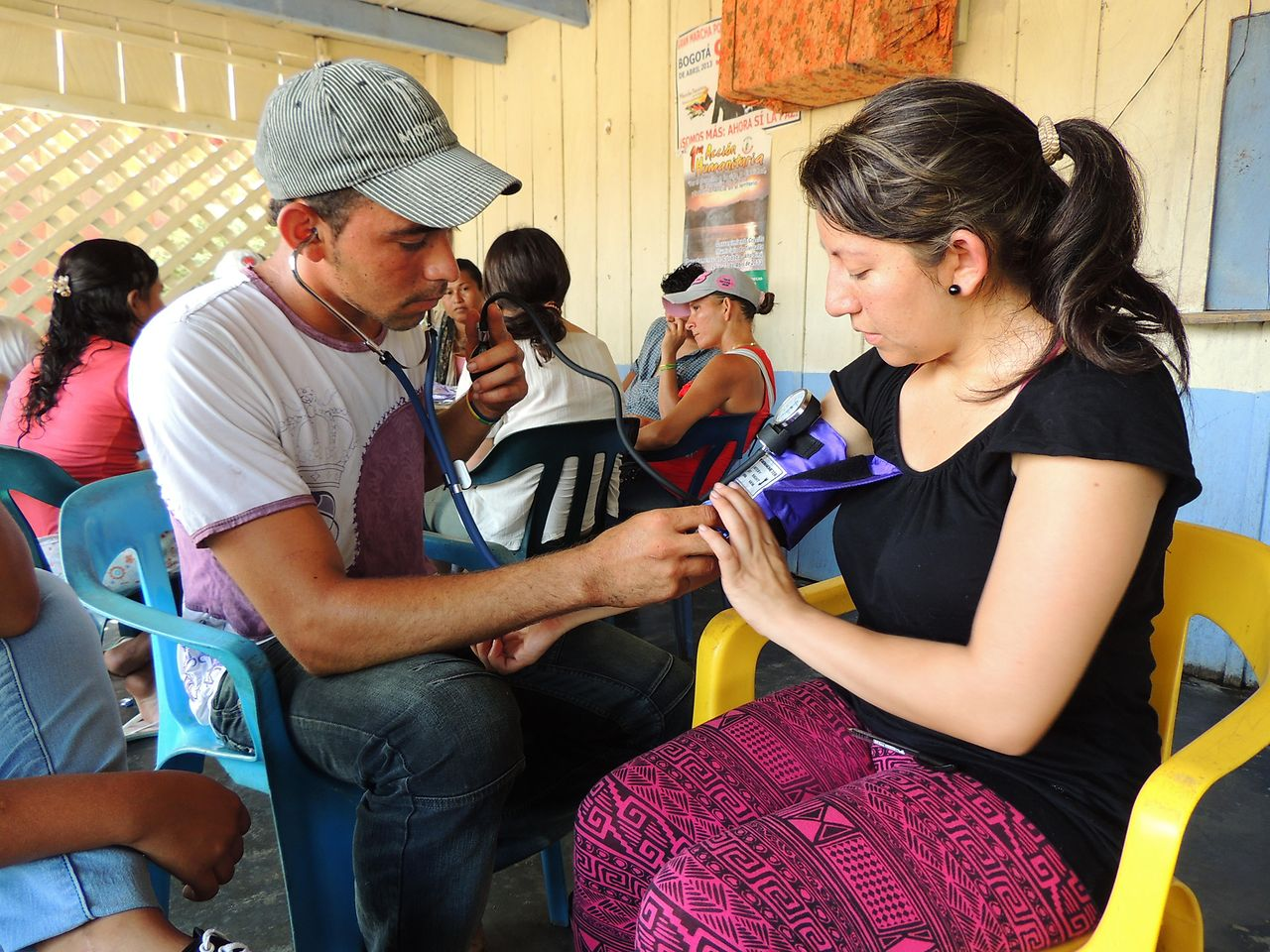 With the help of a medical student (right), a member of the Valle del Río Cimitarra community learns how to measure blood pressure.