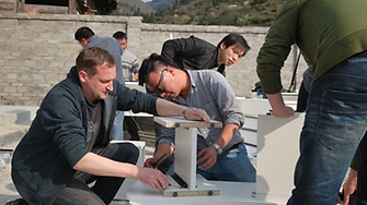 Schneider (left) and his team set up the donated furniture