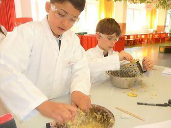Kind reibt Kartoffeln klein