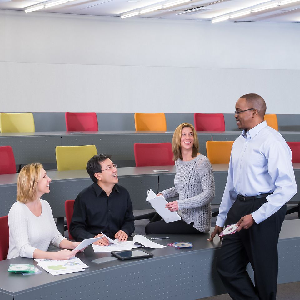 A standing employee is talking to three sitting employees.
