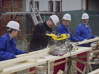 For the roof structure, the volunteers cut several wooden slats with a circular saw.