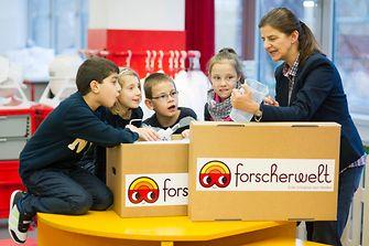 Die Kinder der Theodor Heuss Grundschule inspizieren mit ihrer Lehrerin den Inhalt der Forscherkiste.
