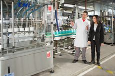 A male employee is presenting a production line to a female employee.