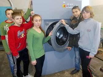 Foster children pose with the donated industrial washing machine