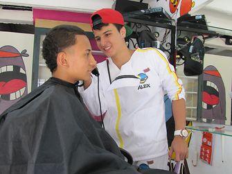 Siempre sonriendo: Duver corta el cabello a uno de sus clientes.