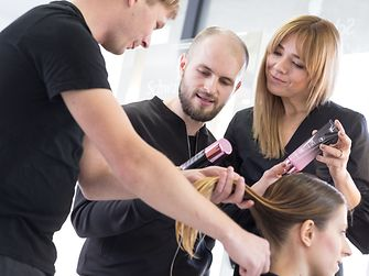 Hairdressers inspect hair structure before product application.