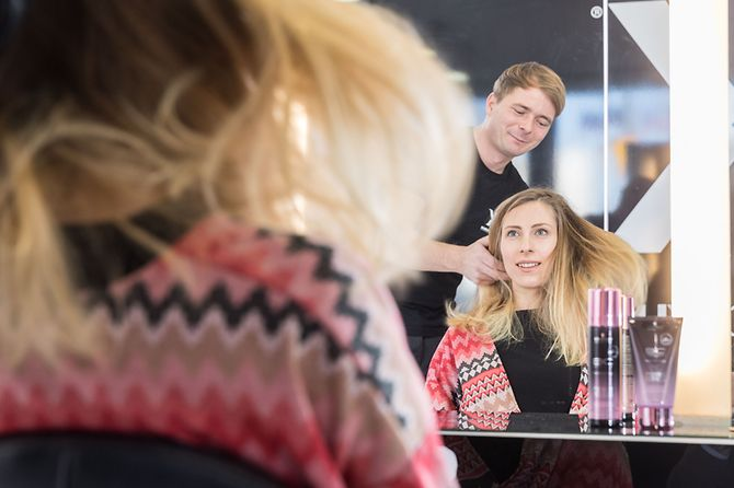 Hairdresser is styling female customer's hair.