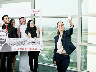 Diverse employees are taking a selfie for Henkel's 140 years celebration.