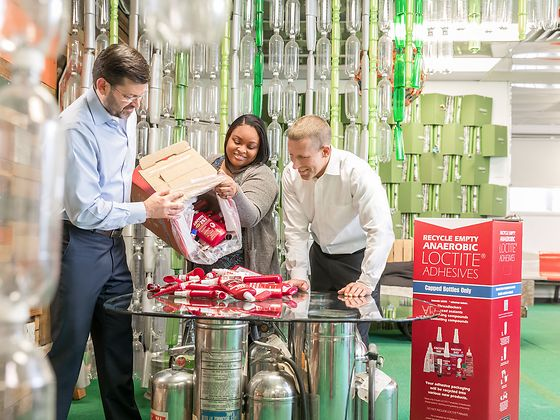 Rhandi Goodman demonstrating how to handle the recycling boxes to her project partners from Henkel, Simon Mawson (left) and Chris Stanford