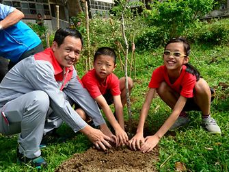 """Tom Lo and his colleagues from Henkel in Taiwan are planting """"Trees of Hope"""" together with school kids."""