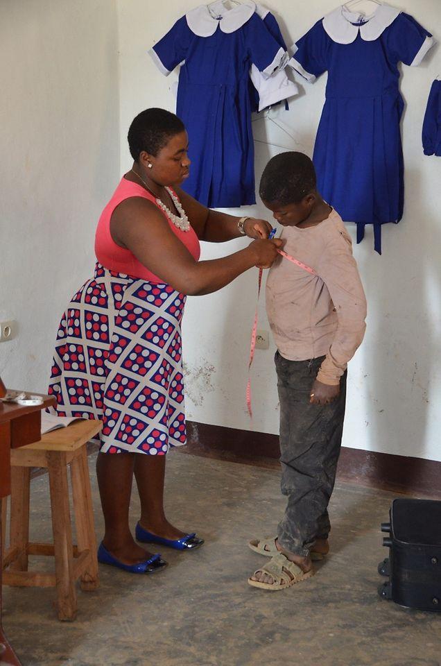 Die Näherin nimmt Maß für eine neue Schuluniform