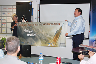 Marcia Lindstrom of NASA and Mark Olsen of OrbitalATK present Henkel with a commemorative banner for their partnership in creating materials used in NASA's Space Launch System (SLS) project.