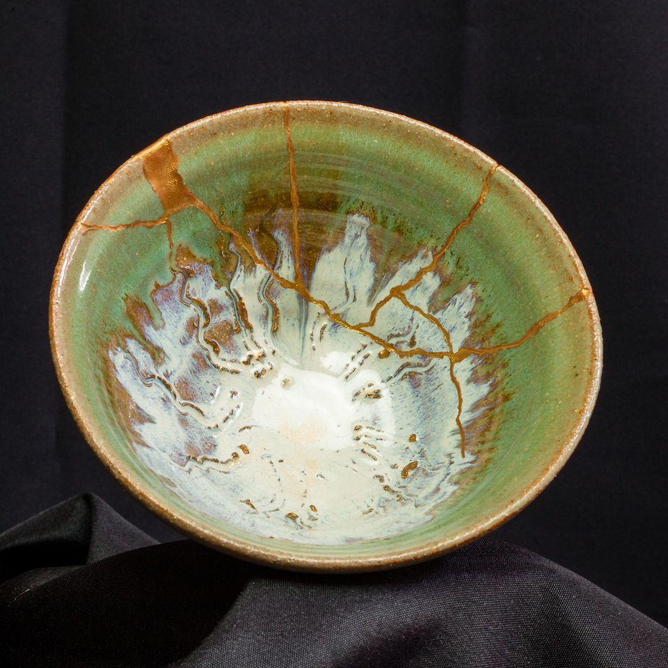 Le Kintsugi est une méthode traditionnelle japonaise de réparation de la céramique. Elle consiste à laisser ressortir les imperfections apparentes de la réparation en utilisant des pigments dorés ou argentés dans la résine.