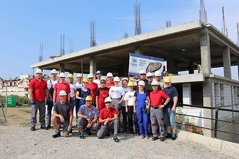 Die 22 Henkel-Mitarbeiter im mazedonischen Veles vor dem Rohbau des Mehrfamilienhauses