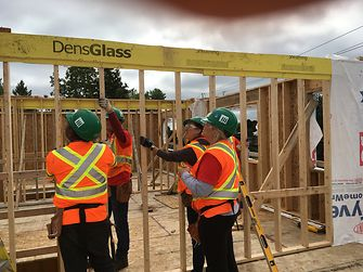 Henkel employees work with precision to put framing in place for Habitat for Humanity® townhouses in Canada.