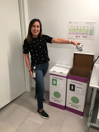 A Henkel employee demonstrates how to properly recycle salon waste using the various bins provided by Green Circle Salons.
