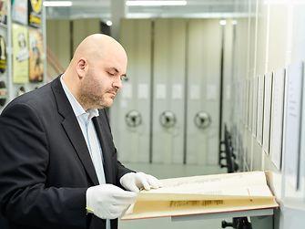 Der Geschichte von Henkel auf der Spur: Archivar Benjamin Obermüller blättert durch ein altes Schriftdokument.