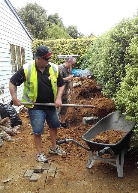 Henkel employees shoveling mulch and loading them into wheelbarrows.