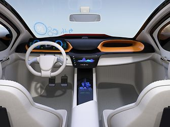 The interior of a future electric vehicle, drivers wheel, windscreen and displays on it from the perspective of the backseat