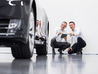 Two men contemplating a car