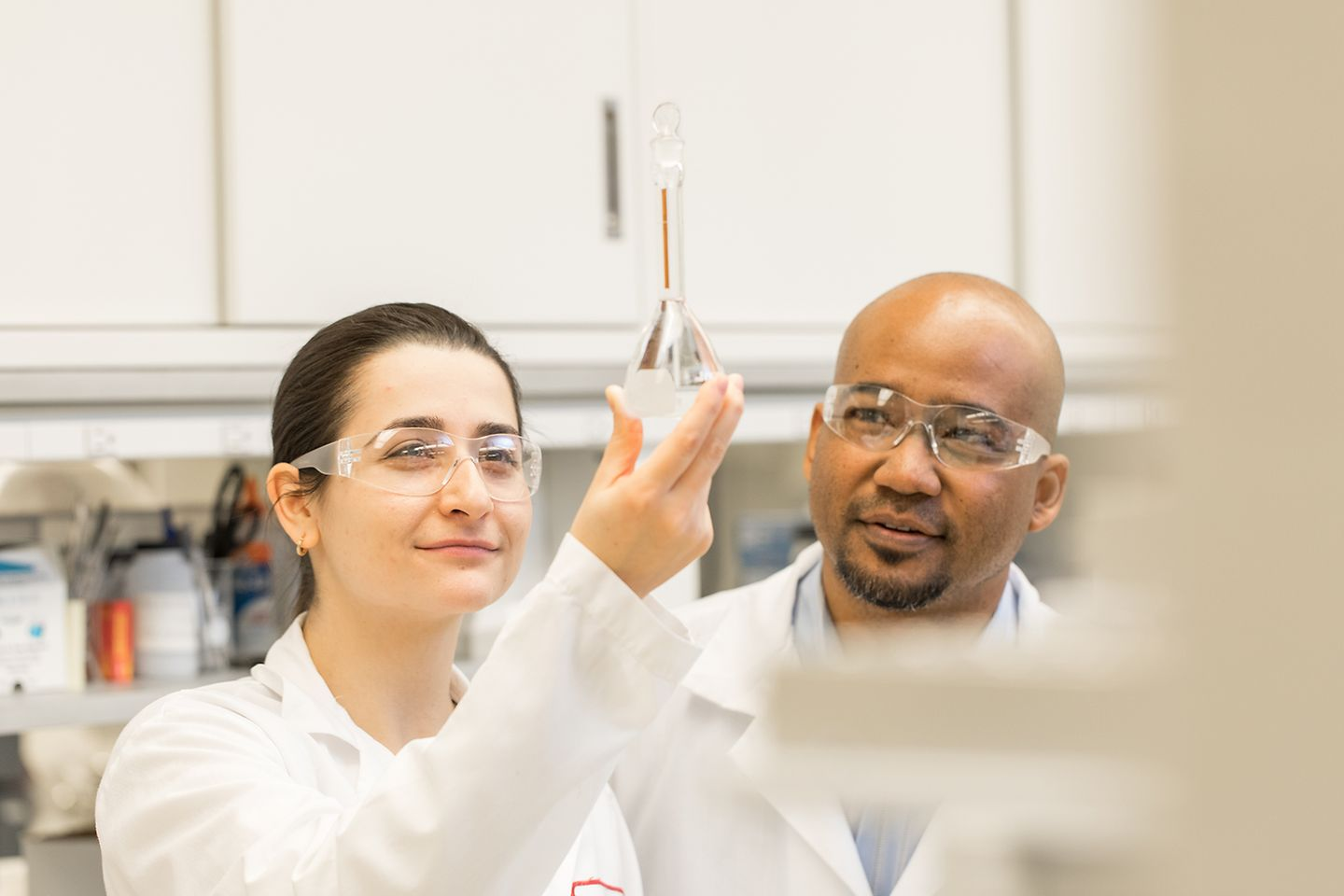 A female and a male lab worker contemplate a liquid in a vial