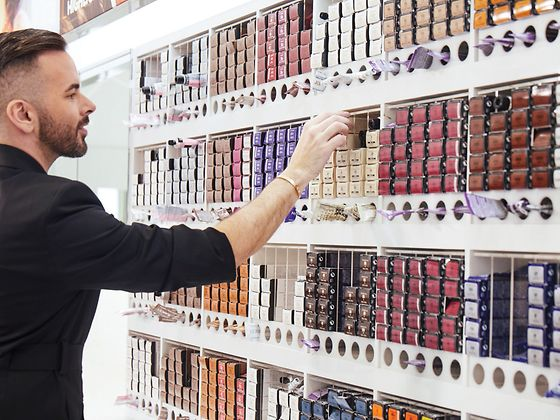 A young man choosing a hair color product from an extensive shelf of packages