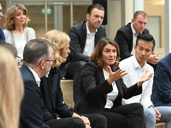 Sylvie Nicol, Executive Vice President Human Resources at Henkel sitting and talking, surrounded by several Henkel employees