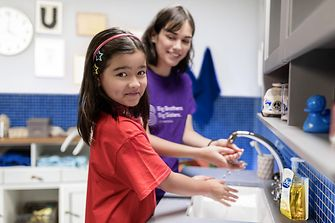 A girl with her 'Big Sister' in a bathroom, washing their hands with Dial soap