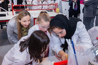 Dr. Simone Bagel-Trah, Chairwoman of the Supervisory Board and the Shareholders' Committee of Henkel, watching kids while conducting experiments